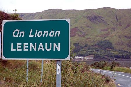 Ortsschild von Leenaun, An Líonán ist die gälische Version. Im Hintergrund das Dorf, das am Kopf vom Killary Harbour liegt, des einzigen Fjords Irlands, Connemara, Co Galway, Westirland