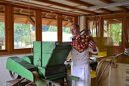 Odenwald - Der Apfelwein-Professor bei der Arbeit: Peter Merkel füllt Äpfel in seine alte Pressmaschine