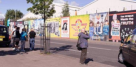 Nordirland - Touristen bestaunen die Wandbilder an der Falls Road in Belfast