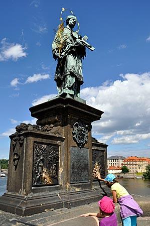 Tschechien - Prag - Die Statue des Hl. Nepomuk auf der Karlsbrücke. Messingplatten erzählen seine Geschichte. Wenn man den stürzenden Märtyrer mit den Fingern berührte, bringe es Glück, sagen die Prager.