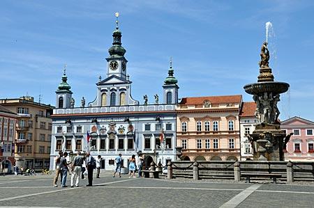 Marktplatz von Budweis mit dem dreitürmigen hellblauen Rathaus und dem Samson-Brunnen
